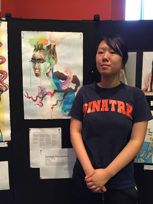 FSSA Senior Hui Ting Lan stands beside her painting in the school's atrium.