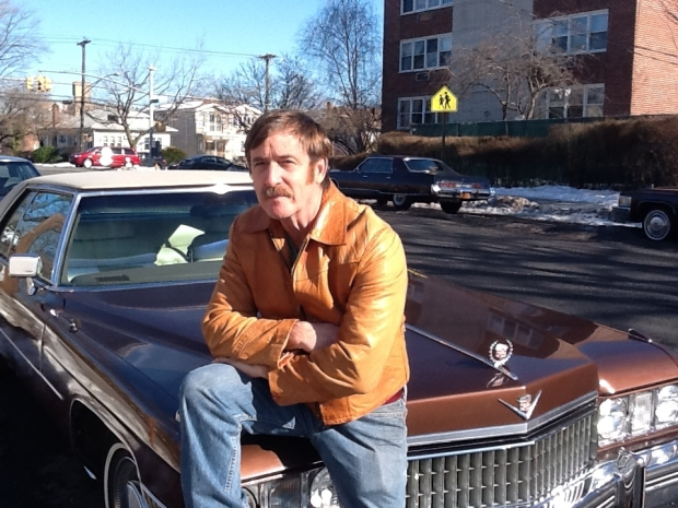 Mr. Brozen posing next to a Cadillac.