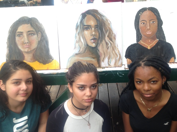 Sophomore students pose next to their self portraits which will be on display at Socrates Sculpture Park in May.